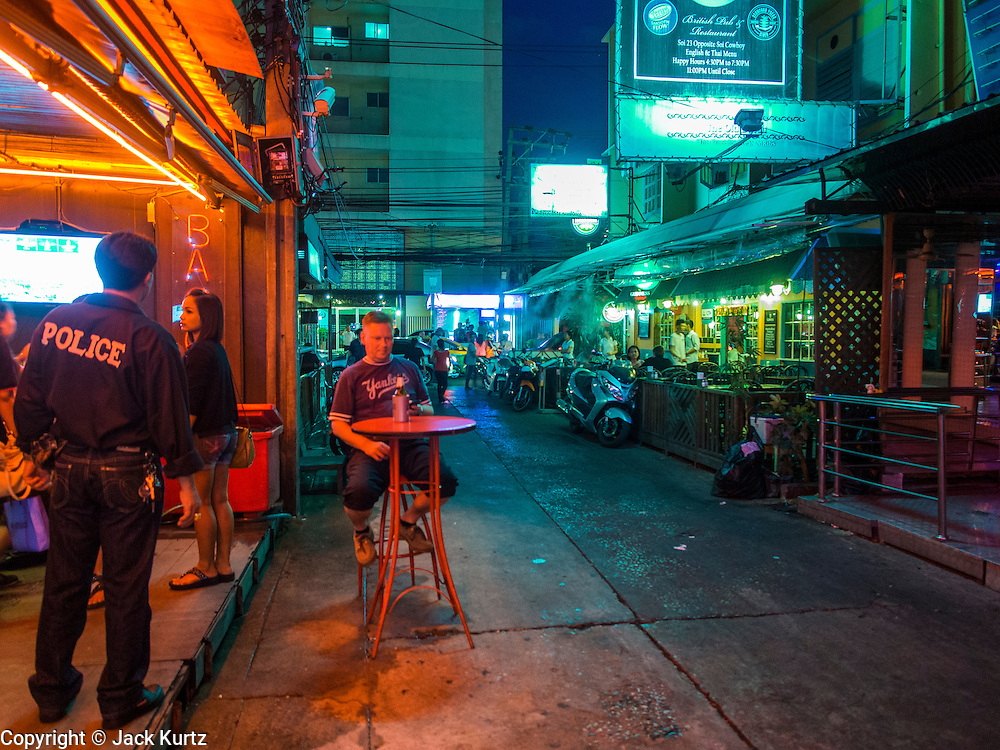 """22 MAY 2014 - BANGKOK, THAILAND: A foreigner drinks a beer at a bar on Soi Cowboy, one of Bangkok's """"adult entertainment"""" districts, after the Thai army announced an overnight curfew. The Thai army suspended civilian rule, suspended the constitution and declared the """"military takeover of the nation."""" The announcement came just before evening as a meeting between civilian politicians and the army was breaking up with no progress towards resolving the country's political impasse. Civilian politicians were arrested when the meeting ended. The army also declared a curfew from 10PM until 5AM.    PHOTO BY JACK KURTZ"""