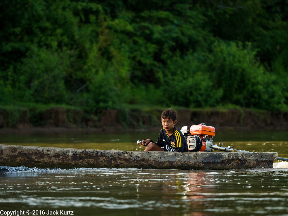 22 JUNE 2016 - DON KHONE, CHAMPASAK, LAOS: A boy drives his canoe up the Mekong River past Don Khone in the 4,000 Islands area of southern Laos. Don Khone Island, one of the larger islands in the 4,000 Islands chain on the Mekong River in southern Laos. The island has become a backpacker hot spot, there are lots of guest houses and small restaurants on the north end of the island.         PHOTO BY JACK KURTZ
