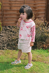 Young girl with autism standing outside in garden playing with lip,