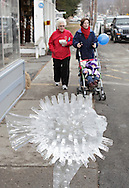 Wurtsboro, New York  - An ice sculpture is on display in front of a store as people walk on the sidewalk in the background during the Wurtsboro Winterfest on Feb. 11, 2012. ©Tom Bushey / The Image Works
