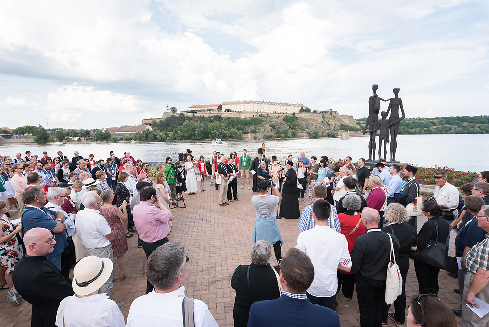 """3 June 2018, Novi Sad, Serbia: Participants of the CEC assembly gather in a peace prayer on the Danube.  Commemoration, forgiveness, and hope were at the focus of the prayer. A procession of delegates and participants started at the memorial commemorating the victims of the raid on Novi Sad in January 1942 during World War II. Hungarian armed forces occupying the region killed 1,246 civilians of the city, mainly Serbs and Jews, throwing their bodies into the Danube. The procession then passed underneath Varadinski Bridge and ended at the newly constructed Žeželj Bridge. At the end of the procession four trees were planted near Žeželj Bridge as a sign of hope and reconciliation. The Conference of European Churches General Assembly takes place on 31 May - 6 June 2018, in Novi Sad, Serbia. More than 400 delegates, advisors, stewards, youth, staff, and distinguished guests take part in the 2018 General Assembly and related events. Gathered together under the theme, """"You shall be my witnesses,"""" the assembly forges the path for CEC for the coming five-year period and beyond. Of central concern is the future of Europe in light of economic, political, and social crises and how the churches will live out a vision of witness, justice, and hospitality within this context."""