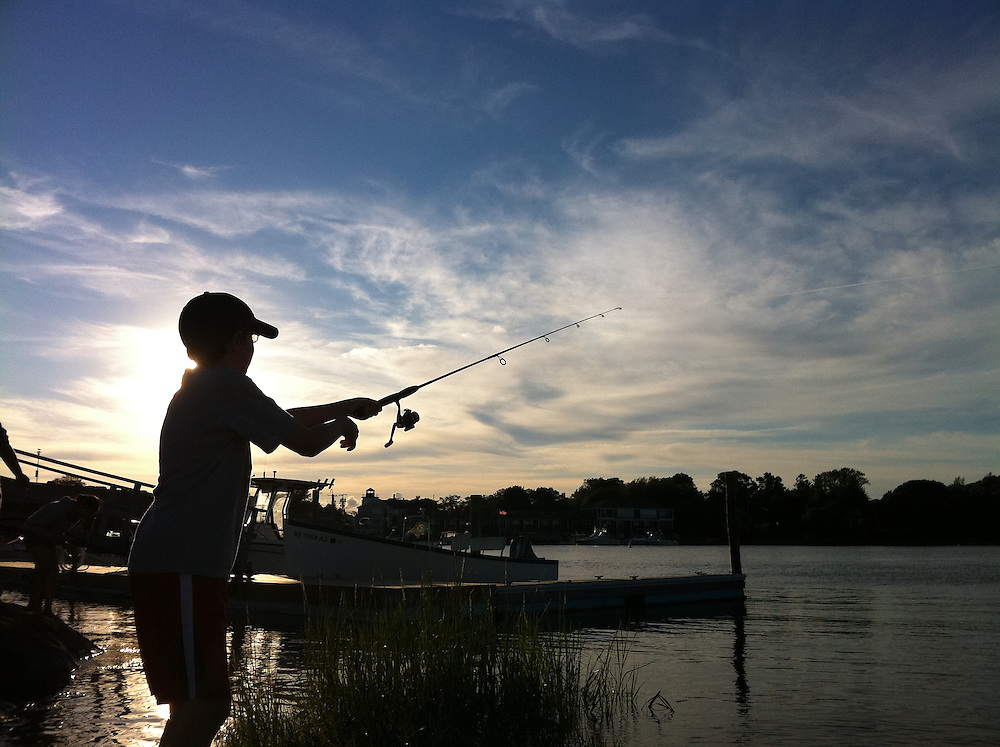 Silhouette of a young boy fishing by the Bass River in Cape Cod, in the northeast.  Copyright John O'Boyle<br /> john@johnoboyle.com