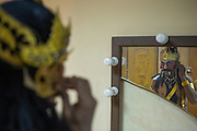 A performer fixes his headdress in front of a mirror before a show of 'wayang orang', or 'human puppets', at Bharata Purwa theater in Central Jakarta, Indonesia. 'Wayang orang' is a classical Javanese form of performing art which combines dances and drama to represent episodes of the Ramayana and Mahabharata epics.