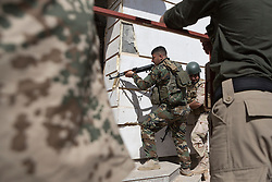 © Licensed to London News Pictures. 09/03/2015. Erbil, Iraq. A Kurdish peshmerga fighter, watched by German army instructors (left and right), covers a doorway during a urban warfare training on at a partially finished housing estate near Erbil, Iraq.<br /> <br /> The training is part of a four week platoon level infantry training package run by coalition forces aimed at improving the efficiency of the Iraqi Security Forces. Photo credit: Matt Cetti-Roberts/LNP