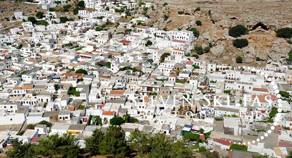 Rhodes. Greece. Above and close up view of dazzling medieval whitewashed village of Lindos. Laying on the slopes of the dramatic Acropolis and Knights castle, the charming and traffic free village of Lindos is a maze of narrow winding black and white tiled alleyways fronted by imposing doorways which lead to flower filled courtyards of the unique Lindian houses which were built by rich sea-captains during the 15th  and 18th century's. Lindos is located on the east coast of the island of Rhodes which is the largest of the Dodecanese Island group and one of the most popular Greek Islands.
