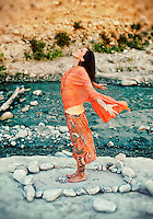 """Woman outdoors near a river standing in a rough mandala of stones with her arms and heart open.<br /> :::<br /> """"The aim of life is to live, which means to be aware—joyously, drunkenly, serenely, divinely aware."""" Henry Miller"""