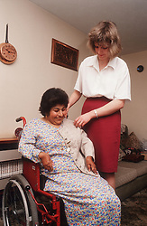 Carer helping woman with disability; who is wheelchair user; to get dressed,