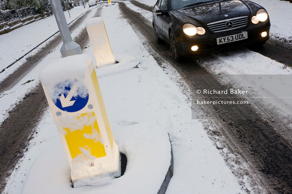 Illuminated road bollards and passing Mercedes car during wintry snows in south London.