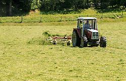 THEMENBILD - ein Landwirt mit Traktor und Maehwerk beim Heuwenden, aufgenommen am 10. Juli 2015, Leogang, Österreich// a farmer with tractor and mower, turn around the hay, Leogang, Austria on 2015/07/10. EXPA Pictures © 2015, PhotoCredit: EXPA/ JFK