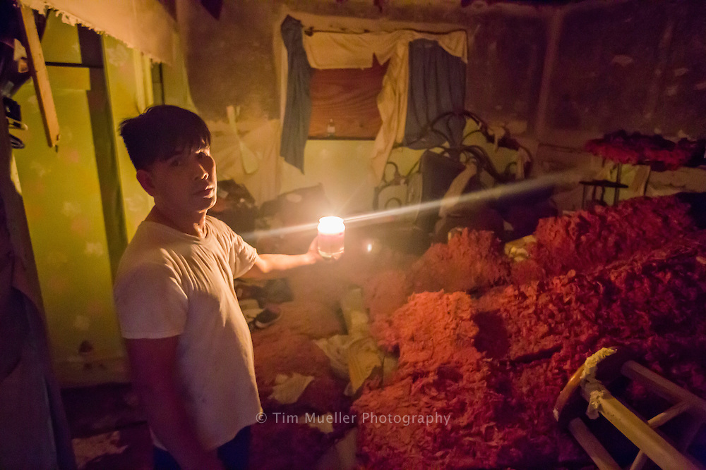 Reagan Nguyen uses a candle Wednesday, August 17, 2016 to survey the damage to his duplex. Nguyen has never experienced flooding in the 18-years he has lived in the duplex located near the intersection of Prescott Road and Tracy Avenue.