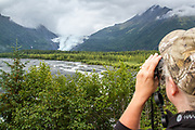 A visitor uses binoculars to get a better look at a glacier near Seward, Alaska.