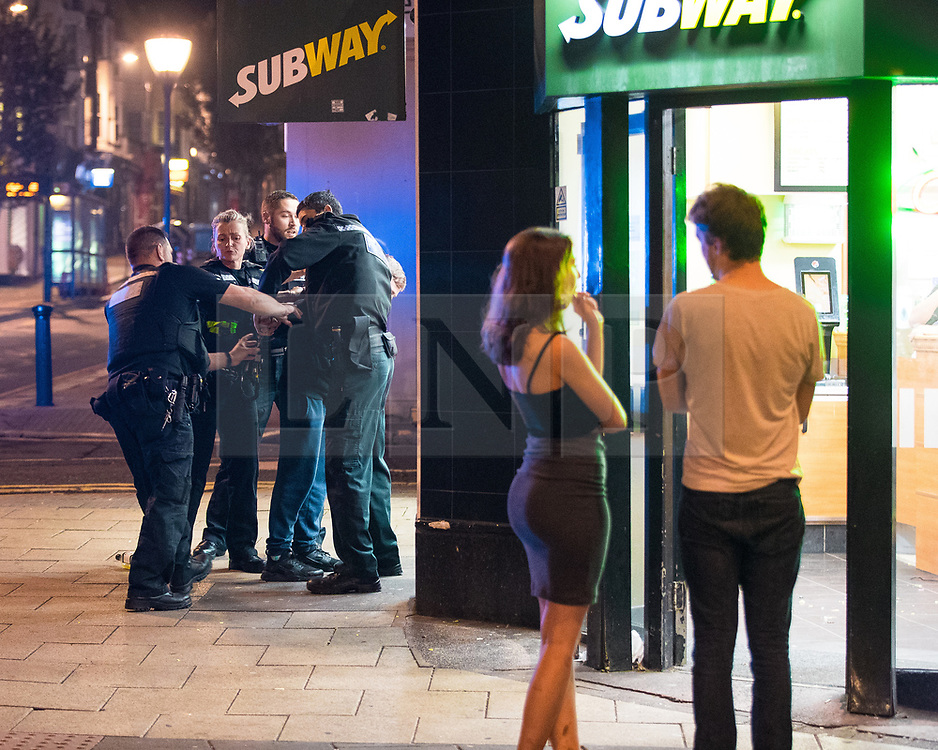 © Licensed to London News Pictures . 26/09/2017. Brighton, UK. Police detain and handcuff a man outside a branch of Subway after a fight in Steine Gardens in the Kemptown area of the city . Revellers at the end of a night out in Brighton during Freshers week , when university students traditionally enjoy the bars and clubs during their first nights out in a new city . Photo credit: Joel Goodman/LNP