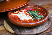 Shakshouka (also spelt: shakshuka, shaqshuqa, chakchouka) a Middle Eastern dish consisting of poached or fried eggs cooked in a sauce of tomatoes, bell peppers, onions, and spices