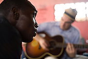 Member of the band King's Jubilee, Terry Williams (left), sings during a jamming session with Canadian artist Dave Bidini (back) at the Buduburam refugee settlement, roughly 20 km west of Ghana's capital Accra on Friday April 13, 2007. The group, which is composed of five Liberian men living at Buduburam, is currently recording their second album, and already has a growing number of fans back in Liberia. The Buduburam refugee settlement is still home over 30,000 Liberians, most of which have mixed feelings about returning to Liberia..