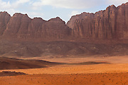 Red sand desert and jagged sandstone cliffs in Wadi Rum, Jordan.