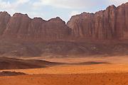 Red sand desert and jagged sandstone cliffs in Wadi Rum, Jordan.