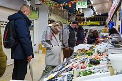 © Licensed to London News Pictures. 13/12/2020. London, UK. Shoppers at a fishmonger in north London amid fears of UK facing a shortage of fish if EU-UK trade negotiations do not reach an agreement on fishing rights. Brexit talks continue as fishing remains one of the biggest issues in the  trade negotiations. Prime Minister Boris Johnson warns a no-deal remains the most likely outcome.  Without a deal, fishing boats from the European Union would be banned from fishing in the UK's Exclusive Economic Zone (EEZ) and UK fishing boats would be barred from the entering waters of nearby EU member states. Photo credit: Dinendra Haria/LNP