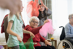 Girls with senior woman doing gentle sports exercise with cloth in rest home