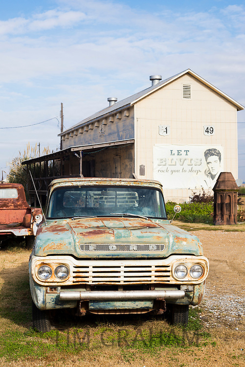 Old Ford pickup truck by cotton gin and Elvis sign at The Shack Up Inn cotton pickers themed hotel, Clarksdale, Mississippi USA