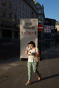 With a further 149 reported dying from Coronavirus in the last 24hrs, taking the UK death toll to 43,320, a masked Londoner eating ice cream walks past social distance advice rules on Regent Street during the Covid pandemic, on 25th June 2020, in London, England.