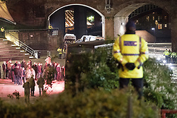 """© Licensed to London News Pictures . 03/11/2017 . Manchester , UK . Police watch on as fans of Tommy Robinson (real name Stephen Yaxley-Lennon ) queue for signed books at the launch of the former EDL leader's book """" Mohammed's Koran """" at Castlefield Bowl . Originally planned as a ticket-only event at Bowlers Exhibition Centre , the launch was moved at short notice to a public location in the city . Photo credit : Joel Goodman/LNP"""