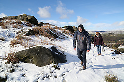 © Licensed to London News Pictures. 02/03/2016. Ilkley, UK. Walkers make their way up onto a snowy Ilkley Moor after heavy snow fall in Yorkshire this morning.  Forecaster are predicting more snowfall and strong winds as Storm Jake moves in. Photo credit : Ian Hinchliffe/LNP