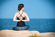 Christina practicing some early springtime yoga on the rocks in Narragansett, Rhode Island, with nothing but warm sun and the sound of ocean waves.