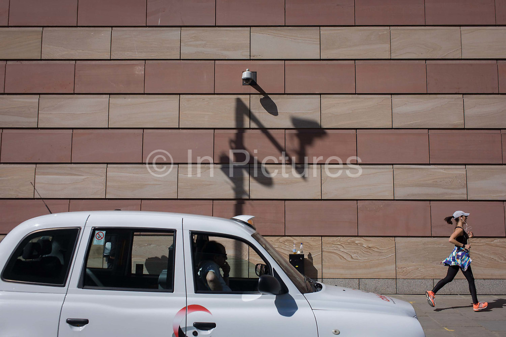 A lady jogger is watched by a taxi driver below a CCTV camera with the shadow of a traffic camera on the wall of a modern office building in the City of London, the capital's financial district. The capital's financial district - aka the Square Mile - is the oldest, historic quarter, home to banking, financial and insurance institutions and therefore victim to street security problems as well as white collar crime. The City is therefore one of the most covered areas in Britain for CCTV surveillance cameras, introduced during IRA terrorism activity in the 90s but now there to monitor the streets.