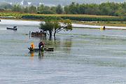 Chinese fishermen fish in a lake near the Old Town of Lijiang, Yunnan, China