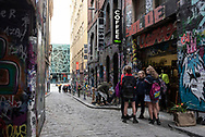 Melbourne, Australia - August 23, 2017: A musician sets up to busk and a small group of students talk on Hosier Lane, an alley famous for its graffiti art in Melbourne, Australia.