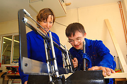 Young man with Downs Syndrome learning how to use saw at a workshop for craftspeople with learning disabilities UK