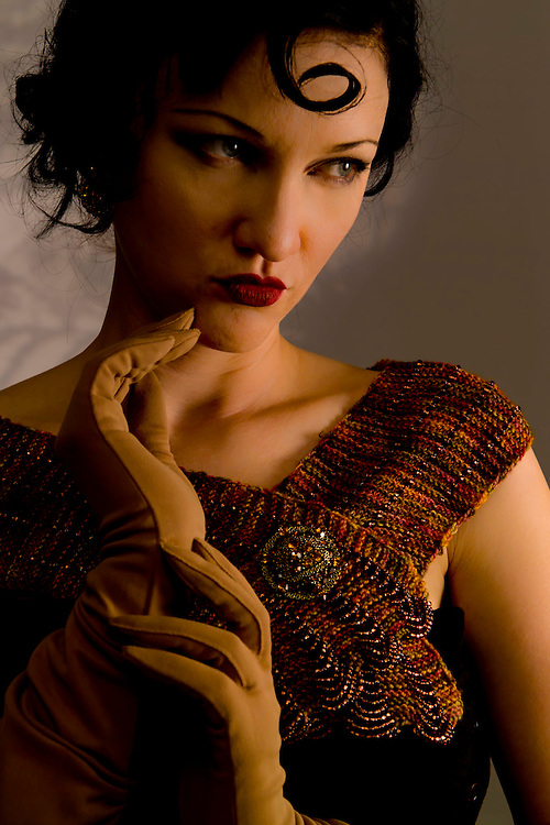 Dana Blue posing for a 1920's themed fashion shot. Brunnete with a curl in the middle of her forehead and bright red lipstick. A mixed yarn sweater stole in orange, brown and black with a rhinstone pin over the left side of chest on sweater. She is holding her right beige gloved hand with fingers just below her chin  while her left gloved hand rests on the base of right hand. She looks away pensively to the left.