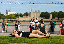 © Licensed to London News Pictures. 05/07/2019. London, UK.  A woman relaxes on the grass during the warm and sunny weather near Tower Bridge in London on Friday lunchtime. The UK continues to enjoy seasonally warm weather this week, but rain is forecast across the country during the next few days. Photo credit: Vickie Flores/LNP