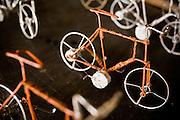 Men make miniature bicycles from metal wire at the Village Artisanal de Ouagadougou, a cooperative that employs dozens of artisans who work in different mediums, in Ouagadougou, Burkina Faso, on Monday November 3, 2008.