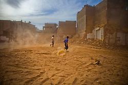 Residents make their way through demolishing site in old city in Kashgar, China.