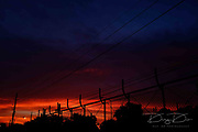 Electrical power line and fence in sunset or sunrise