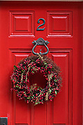 A colorful red wooden door on a historic home decorated with a Christmas wreath on Church Street in Charleston, SC.