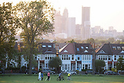 With the tall towers at Nine Elms in the distance, a sun sets below a line of homes and ash trees and a group of friends leave Ruskin Park after a game of cricket, on 13th June 2021, in London, England.