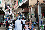 People and motorbikes crowd a narrow street in the Sabra and Shatila Refugee Camps in Beirut, Lebanon. Home to Palestinian refugees, the camps became the site of an infamous massacre in 1982. A poster of Yasser Arafat hangs in the distance.