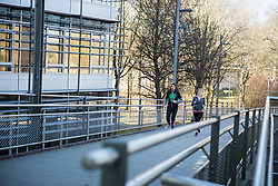 Man and woman jogging on bridge in city