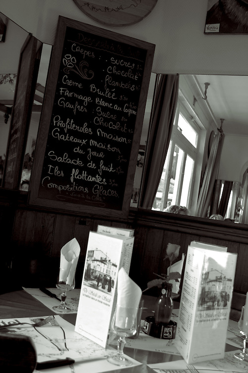 table in french restaurant with menu board overhead,black and white,verticle