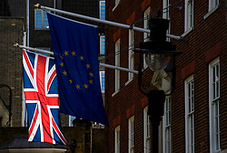 © Licensed to London News Pictures. 30/03/2017. London, UK. The Union Flag, also known as the Union Jack is seen flying behind the The Flag of Europe on Europe House in Westminster. Yesterday (Weds), a letter was officially delivered to the European Council,  triggering Article 50 of the Lisbon treaty. Photo credit: Ben Cawthra/LNP