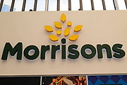 Large overhead signage displaying the brand logo for British supermarket chain Morrisons on 23rd August, 2021 in Leeds, United Kingdom. British supermarket chain Morrisons, which employs over 110,000 staff across its 500 shops, has accepted a £6.3bn $8.7bn takeover bid from US private equity firm Fortress Investment Group.