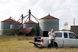 man on cell phone leaning by truck outside an industrial farm in South Carolina
