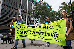 Extinction Rebellion activists protest outside the Department for Environment, Food and Rural Affairs (Defra) against the pollution of the UK's waterways on 5th August 2021 in London, United Kingdom. The activists were highlighting pollution of rivers by water companies and farms and the failure of the Environment Agency and Defra to protect waterways and to prosecute offenders.