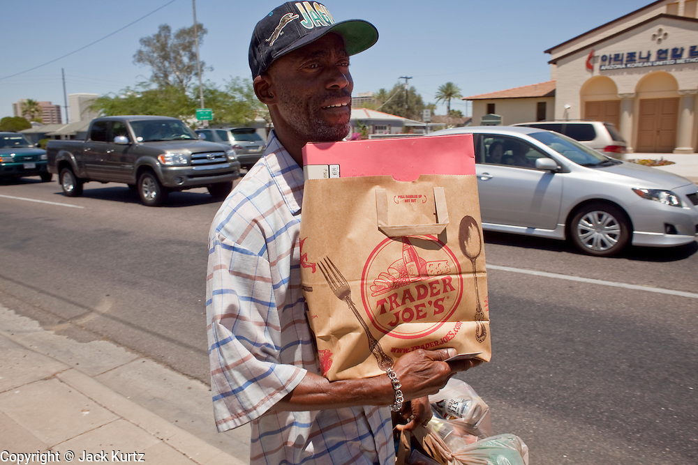 """22 JUNE 2009 - PHOENIX, AZ: Shawn Cooper, who is known on the street as """"Zero,"""" walks back to the Veterans' Administration hospital after picking up some food at the Cultural Cup Food Bank. Zero, an unemployed Army vet, was referred to the food bank by workers at the VA. He said he wouldn't be able to eat regularly without the food bank's help. The Cultural Cup has become a sort of community center. It started as a food bank and has since grown to include a clothing bank and free walk in clinic. The walk in clinic at the Cultural Cup Food Bank started two years ago when Cultural Cup founder Zarinah Awad wanted to expand the food bank's outreach and provide basic medical care for the people who use the food bank. The clinic sees, on average, 7 - 11 patients a week. Awad said that as the economy has worsened since the clinic opened and demand has steadily increased. She attributes the growth to people losing their jobs and health insurance. The clinic is staffed by volunteers both in the office and medical staff. Adults are seen every Saturday. Children are seen one Saturday a month, when a pediatrician comes in. Awad, a Moslem, said the food bank and clinic are rooted in the Moslem tradition of Zakat or Alms Giving, the giving of a small percentage of one's income to charity which is one of the Five Pillars of Islam.   PHOTO BY JACK KURTZ"""