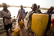 A boy ties a plastic container full of water to the back of his bike as he prepares to head home at the Dikunani dam in Savelugu, northern Ghana, on Friday March 9, 2007. The only of four water sources that has not completely dried out around Savelugu, the pond is used by hundreds of people daily who sometimes walk several kilometers to fetch water. Despite the presence of mesh filters available to people who come get water, cases of guinea worm in the area have gone up sharply in the recent months.