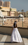Little girl in white dress with beach and tourists in background, Cadiz, Andalusia, Spain