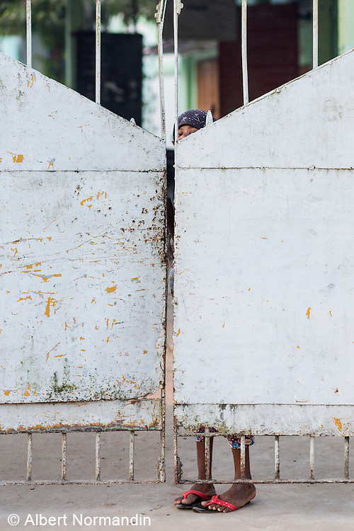 Young girl looking over gate at Mosque. Pathein