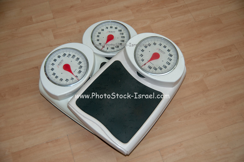 Dieting, weight loss and body image conceptual image of three analogue scales stacked one on top of the other